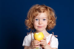 Child with apple. Smiling beautiful child eating apple stock photography