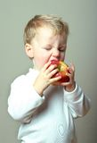 Child and apple. Small child takes a bite out of an apple; diet and nutrition; healthy snack; back to school concept royalty free stock photo