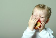 Child and apple. Small child takes a bite out of an apple; diet and nutrition; healthy snack stock photos
