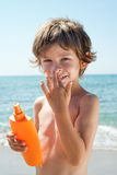 Child apply sun cream on his nose with hands Stock Photos