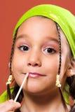 Child applying make-up stock images
