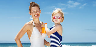 Child applying sunscreen on smiling mother in swimsuit at beach Royalty Free Stock Photography