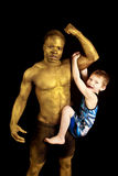 Child on arm. A men painted gold showing off his strength by holding up a young boy by his bicept Stock Photo