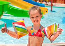 Child with armbands playing in swimming pool Stock Images