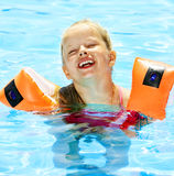 Child with armbands in swimming pool Stock Image
