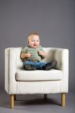 Child in armchair. A happy child sitting in an armchair of light colour Royalty Free Stock Image
