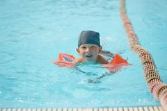 Child in armlets for swimming in an outdoor pool with a water slide. Child in armlets for swimming in an outdoor pool with a water slide Stock Photography