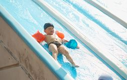 Child in armlets for swimming in an outdoor pool with a water slide. Child in armlets for swimming in an outdoor pool with a water slide Stock Images