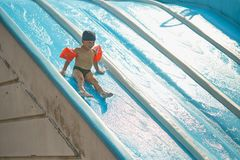 Child in armlets for swimming in an outdoor pool with a water slide. Child in armlets for swimming in an outdoor pool with a water slide Royalty Free Stock Photos