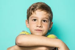 Child with arms folded. Child on blue background with serious face stock photography