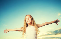 Child with arms outstretched. Freedom. Girl on a background of the sky Stock Photo