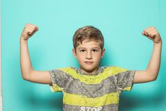 Child with arms raised on biceps. Child with arms raised, marking biceps, on a blue background royalty free stock photos