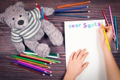 Child arms writing letter to Santa Claus colored pencils. On wooden table Stock Photos