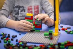 Child arranges block of constructor. a childhood game that develops the imagination of small people. Colorful designer in the hands of a toddler. fun for kids Stock Photography
