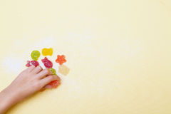 The child arranges marmalade figurines in a marine style. Stock Photos