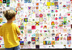 Child Art C. Young child looking at colorful collection of youth art Stock Photography