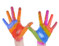 Child Art Hands Painted on White Background. A child is holding up painted art hands on a white isolated background. There are vibrant rainbow colors. Use it for royalty free stock photography