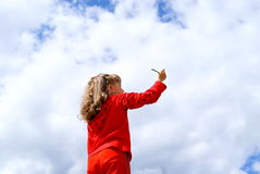 The child - the artist. The girl in red clothes draws a pencil in the sky with clouds Royalty Free Stock Photos
