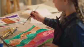 Child artist girl creating abstract watercolour