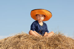 Child from Asia. Boy sitting on straw heaps in the nature Royalty Free Stock Photography