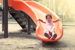 Child asian girl having fun to play slider in playground Stock Photography