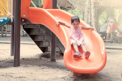 Child asian girl having fun to play slider in playground Stock Images