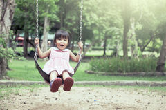 Child asian girl having fun to play swing in playground Stock Images