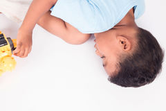child asian little boy lying on the floor and playing toy Royalty Free Stock Photos