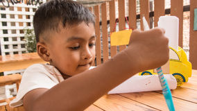 child asian little boy thinking and writing on paper Royalty Free Stock Photo
