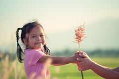 Child asian little girl giving grass flower to her mother. With love in vintage color tone Royalty Free Stock Photo