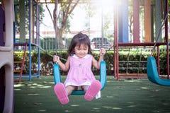 Child asian little girl having fun to play swing. In children playground Stock Photo