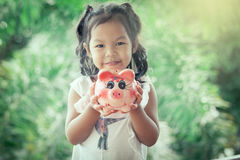 Child asian little girl holding Piggy Bank Royalty Free Stock Photography