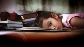Child asian little girl is lying down on book and bored to read. A book in dark tone stock photography
