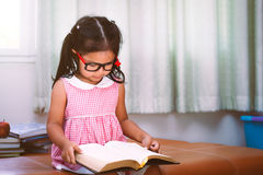 Child asian little girl put on eyeglasses reading a book. In vintage color tone Royalty Free Stock Photo