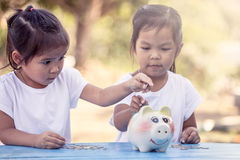 Child asian little girl putting coin into Piggy Bank Stock Images