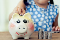 Child asian little girl putting coin into Piggy Bank Royalty Free Stock Photography