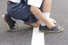 Child Asian tying shoes on the roadside. 1 Royalty Free Stock Image
