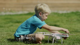 Child assembling modern drone on the green grass lawn. Putting on propellers stock video