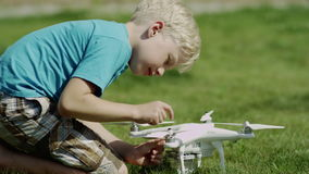 Child assembling modern drone on the green grass lawn. Putting on propellers stock video footage