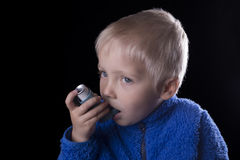 Child and asthma inhaler. Young boy with an asthma inhaler, black background Stock Photos