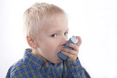 Child and asthma inhaler. Young boy using an asthma inhaler, white background Royalty Free Stock Image