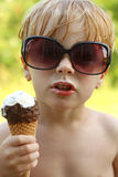 Child with Attitude Eating Ice Cream Cone. A young boy with big sunglasses on gives a bit of attitude while eating ice cream cone stock image