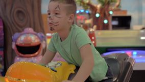 Child is attracted with racing simulator in amusement park. Boy with funny drawn cat face having fun in indoor amusement park. He playing motorbike race stock footage