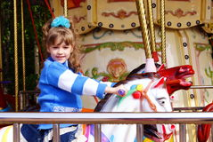 The child on an attraction. The smiling girl goes for a drive on a roundabout-horsy Stock Photography