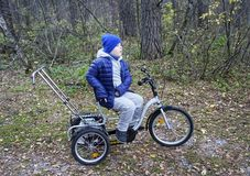 Child autistic with disabilities on a tricycle with management for mom, in a blue cap and jacket in the Park for a walk.  royalty free stock photo