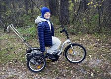 Child autistic with disabilities on a tricycle with management for mom, in a blue cap and jacket in the Park for a walk.  royalty free stock image