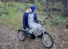 Child autistic with disabilities on a tricycle with management for mom, in a blue cap and jacket in the Park for a walk.  royalty free stock photography