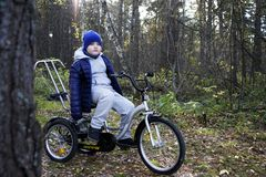 Child autistic with disabilities on a tricycle with management for mom, in a blue cap and jacket in the Park for a walk.  stock image