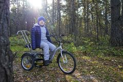 Child autistic with disabilities on a tricycle with management for mom, in a blue cap and jacket in the Park for a walk.  stock images
