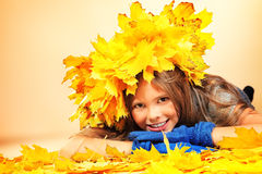 Child autumn. Portrait of a smiling girl in autumn clothes and a hat of maple leaves Royalty Free Stock Images